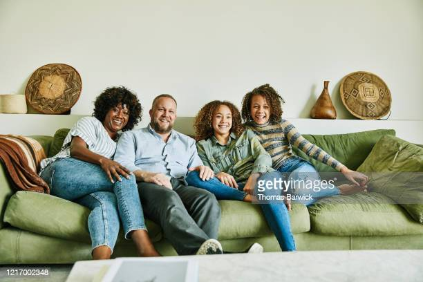 portrait of smiling family sitting on couch in living room - sofa stock pictures, royalty-free photos & images