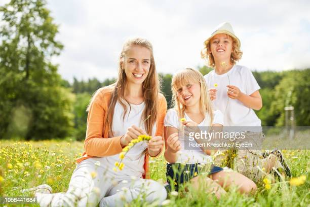 Portrait Of Smiling Family Sitting On Grassy Field At Park