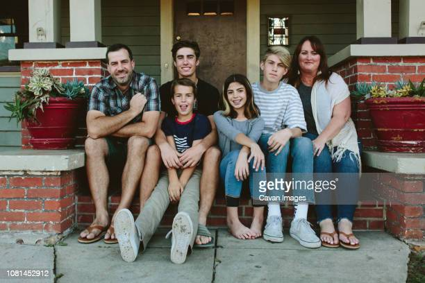 portrait of smiling family sitting on steps by house - voor stockfoto's en -beelden