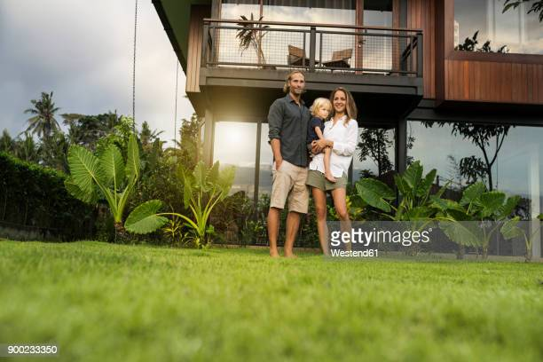 portrait of smiling family standing in front of their design house surrounded by lush tropical garden - facade stock pictures, royalty-free photos & images