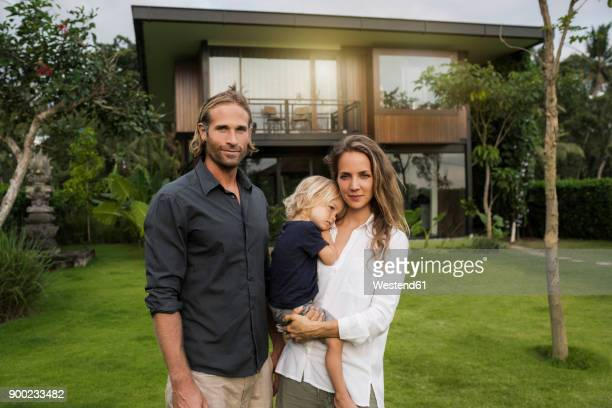 Portrait of smiling family standing in front of their design house surrounded by lush tropical garden