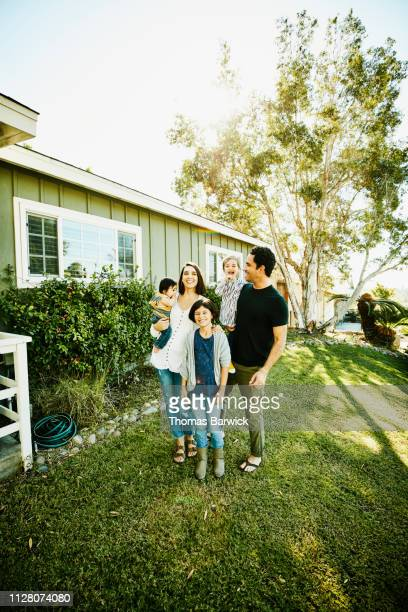 Portrait of smiling family standing in front yard of home