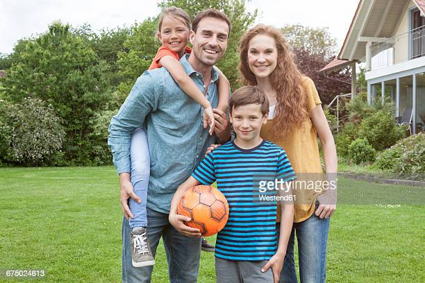 Portrait of smiling family standing in garden