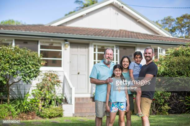 portrait of smiling family standing in lawn - mid adult men stock pictures, royalty-free photos & images