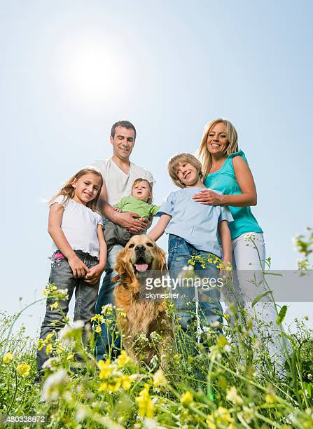 Portrait of smiling family with a golden retriever in nature.