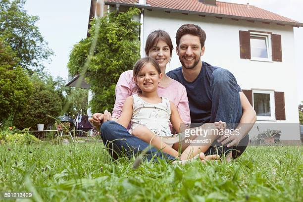 Portrait of smiling family with daughter in garden