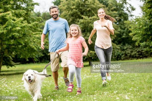 portrait of smiling family with dog running on grassy field against trees in park - one animal stock pictures, royalty-free photos & images