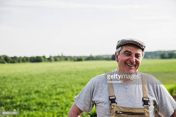 portrait of smiling farmer at a field - farmer stock pictures, royalty-free photos & images