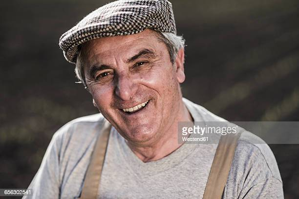 portrait of smiling farmer at a field - flat cap stock pictures, royalty-free photos & images