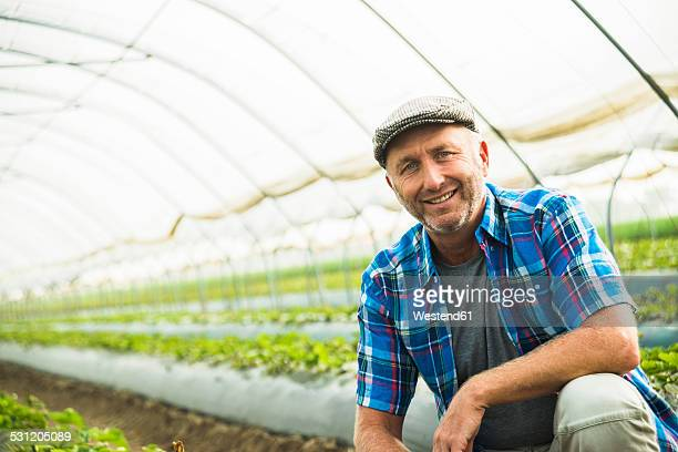 Portrait of smiling farmer crouching in a greenhouse