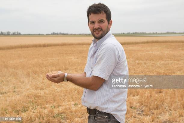 portrait of smiling farmer holding crops while standing on field - 南アメリカ ストックフォトと画像