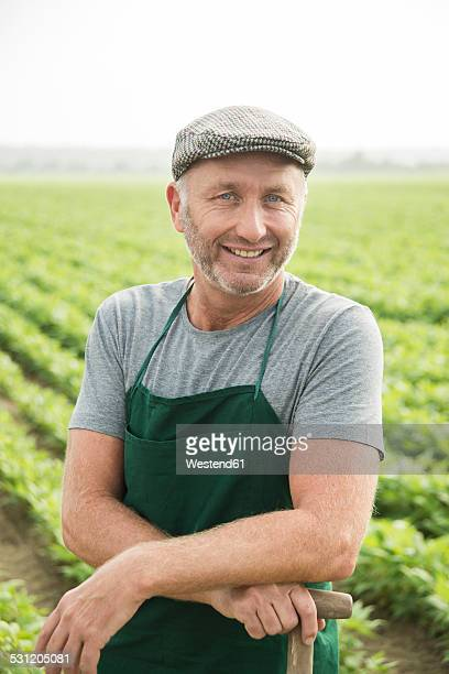Portrait of smiling farmer standing in front of a field