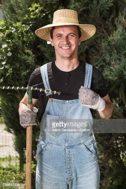 Portrait Of Smiling Farmer With Rake While Standing Outdoors
