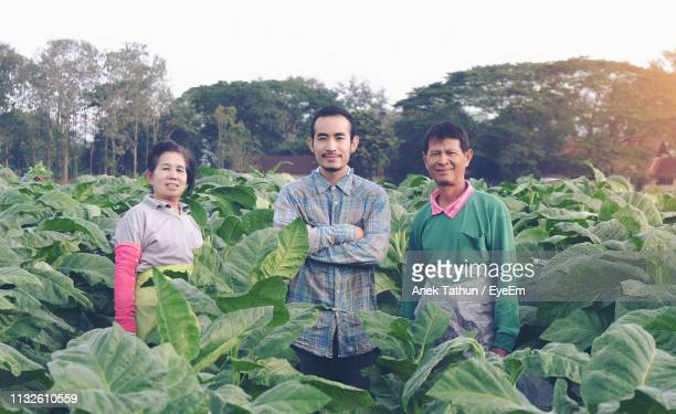 Portrait Of Smiling Farmers Standing Amidst Plants On Field