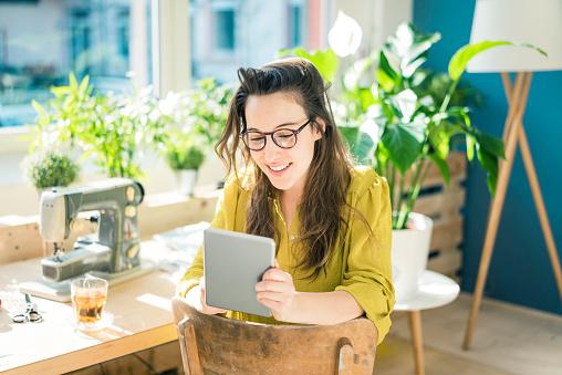 Portrait of smiling fashion designer sitting in her studio using tablet - gettyimageskorea