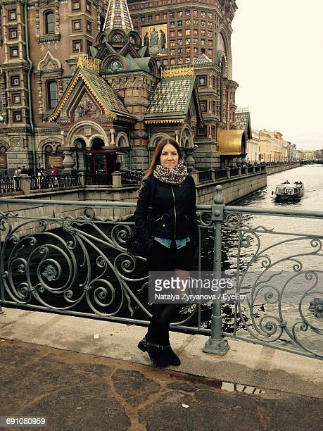 Portrait Of Smiling Fashionable Woman Standing By Railing On Bridge Against Historic Building