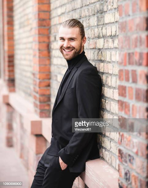 portrait of smiling fashionable young man leaning against brick wall - mock turtleneck stock pictures, royalty-free photos & images