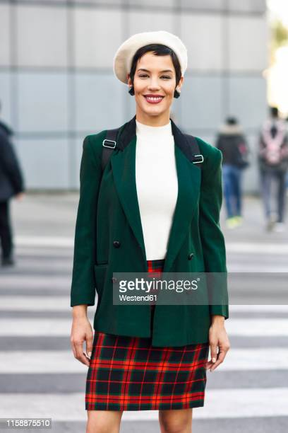portrait of smiling fashionable young woman on zebra crossing - green coat stock pictures, royalty-free photos & images