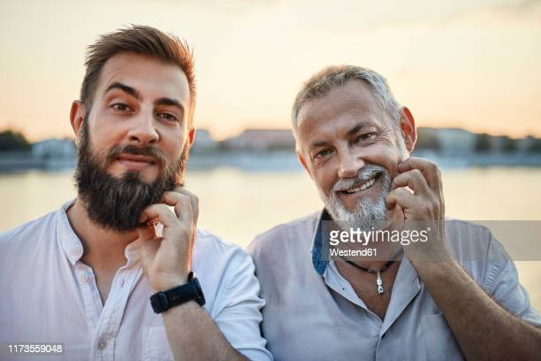 portrait of smiling father and adult son scratching their beards - representar fotografías e imágenes de stock