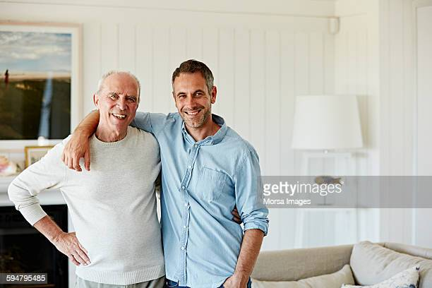 portrait of smiling father and son at home - sohn stock-fotos und bilder