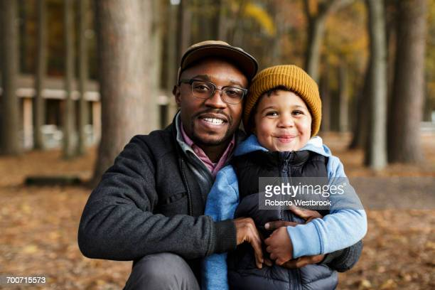 Portrait of smiling father and son hugging in park