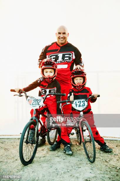 Portrait of smiling father and sons in front of white background before BMX race
