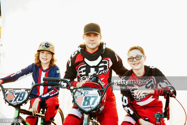 Portrait of smiling father and sons sitting on BMX bikes in front of white background before race
