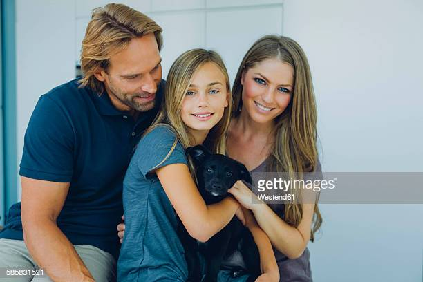 Portrait of smiling father, mother and daughter with puppy