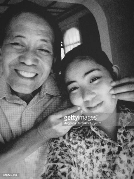 Portrait Of Smiling Father Pinching Daughter Cheeks At Home
