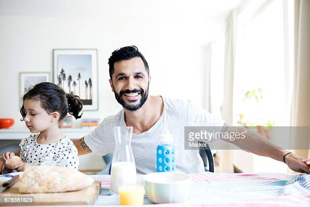 Portrait of smiling father sitting with daughter while having breakfast at home