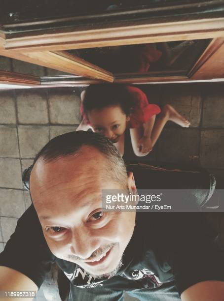 portrait of smiling father with daughter at home - munandar stock pictures, royalty-free photos & images
