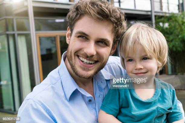 portrait of smiling father with son in front of their home - day 2 stock-fotos und bilder