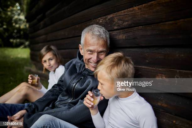 portrait of smiling father with two sons relaxing at wooden hut in garden - genderblend stock pictures, royalty-free photos & images