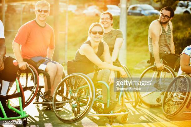 Portrait of smiling female adaptive athlete with friends after basketball game on summer evening