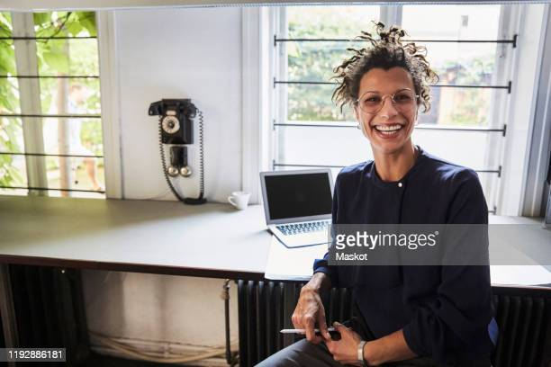 portrait of smiling female architect sitting at table in office - endast en ung kvinna bildbanksfoton och bilder