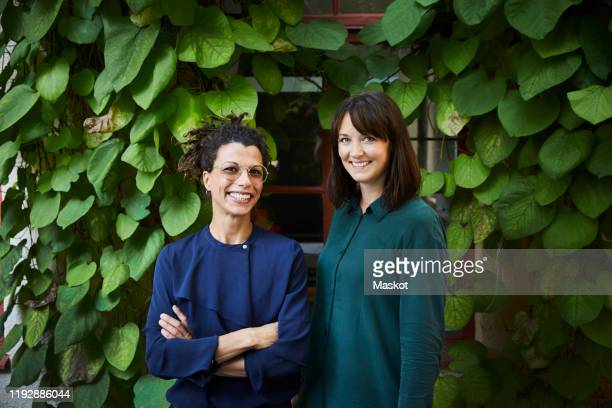 portrait of smiling female architects standing against creeper plants in backyard - 女性建築家 ストックフォトと画像