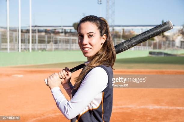 Portrait of smiling female baseball player with a baseball bat