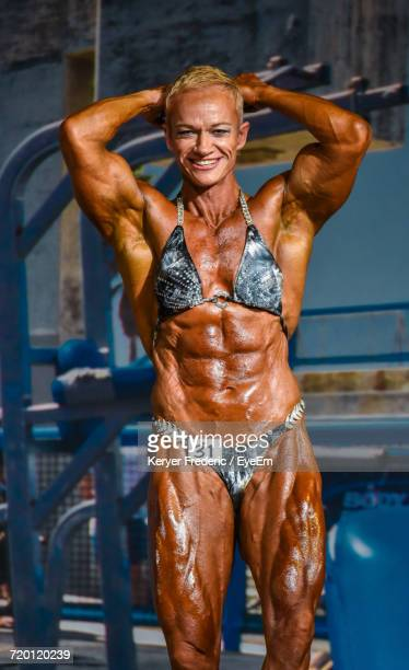 portrait of smiling female body builder standing against equipment - bodybuilding stockfoto's en -beelden
