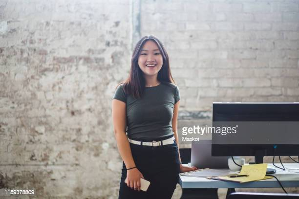 portrait of smiling female computer programmer standing beside desk at creative office - vanguardians stock pictures, royalty-free photos & images
