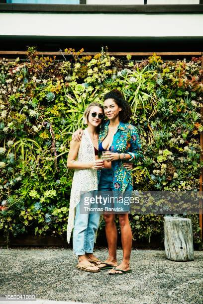 Portrait of smiling female couple embracing in front of living wall