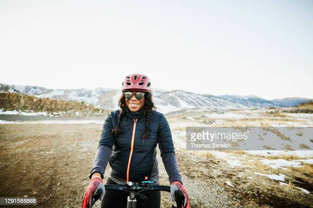 portrait of smiling female cyclist riding gravel bike at sunset on winter evening - active lifestyle stock pictures, royalty-free photos & images