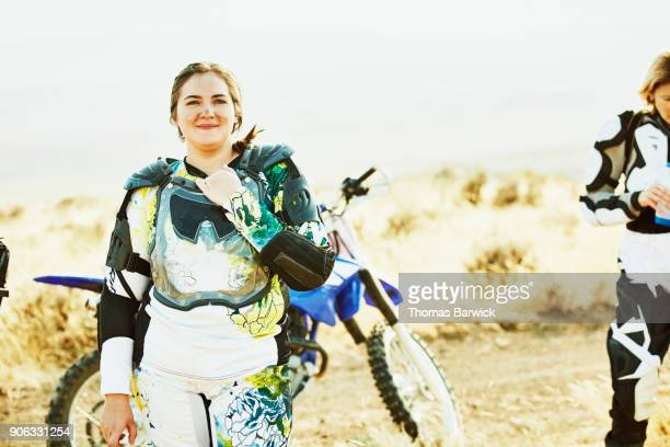 Portrait of smiling female dirt bike rider with dirt on face resting during desert ride