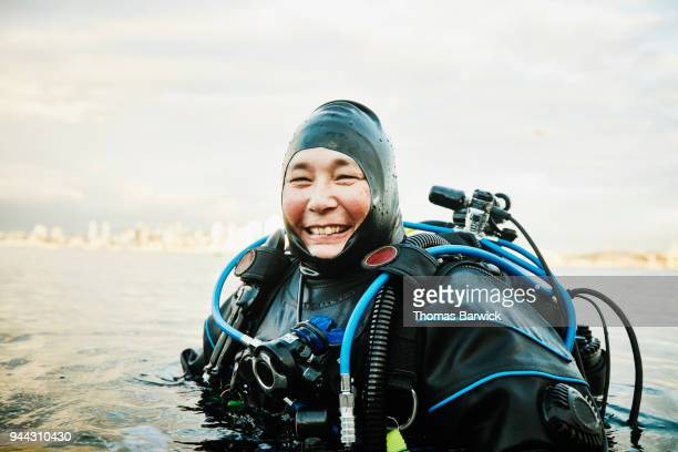 Portrait of smiling female diver standing in water before open water dive