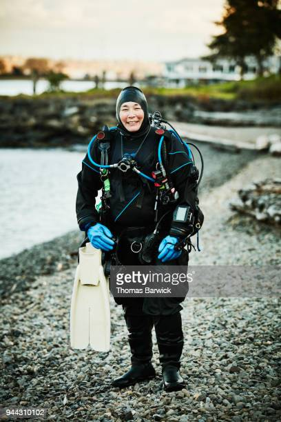 Portrait of smiling female diver standing on beach after open water dive