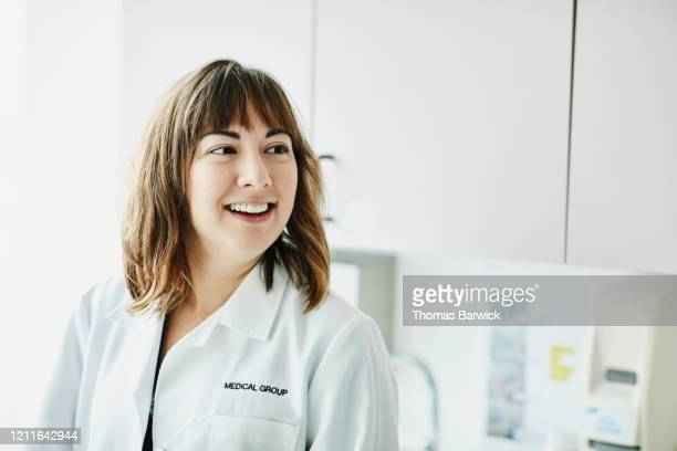 portrait of smiling female doctor in exam room - clinic stock pictures, royalty-free photos & images