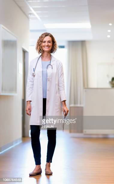 portrait of smiling female doctor with clipboard - full length stock pictures, royalty-free photos & images