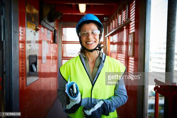 portrait of smiling female engineer in reflective clothing at construction site - eye protection stock pictures, royalty-free photos & images