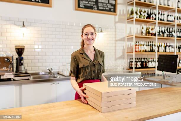 portrait of smiling female entrepreneur standing behind counter - stack stock pictures, royalty-free photos & images