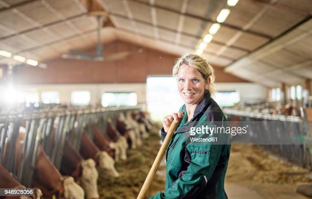 Portrait of smiling female farmer in stable on a farm