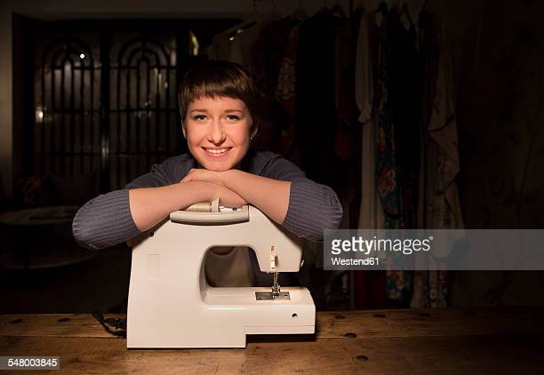 Portrait of smiling female fashion designer leaning on sewing machine at her studio
